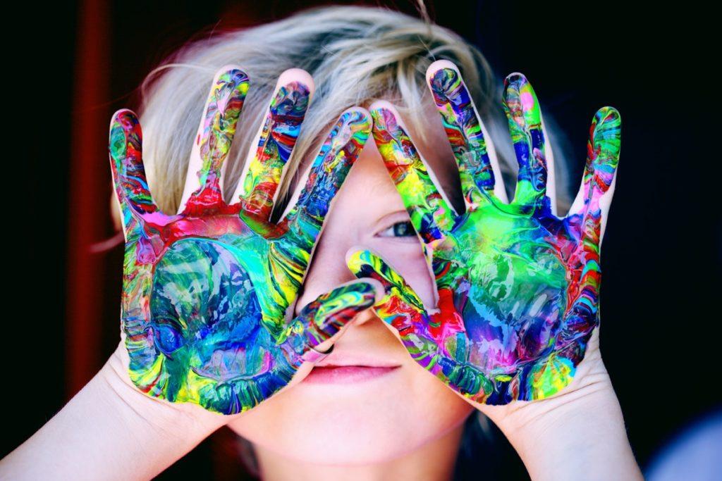lapsi ja värikkäästi maalatut kädet