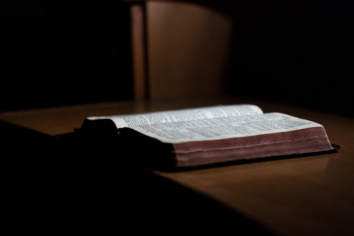 vanha kirja pimeässä huoneessa pöydällä